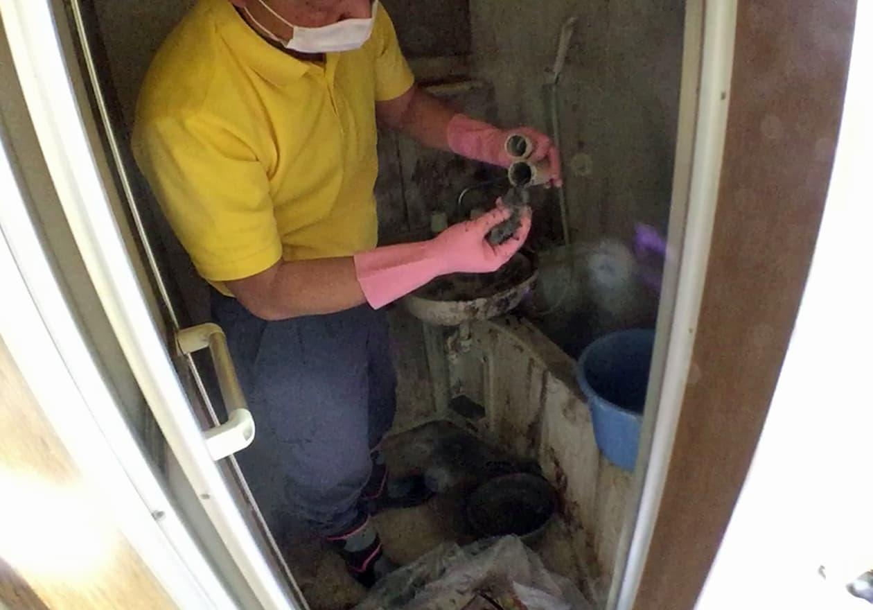 手洗い場の配管詰まりを直している竹内の様子
