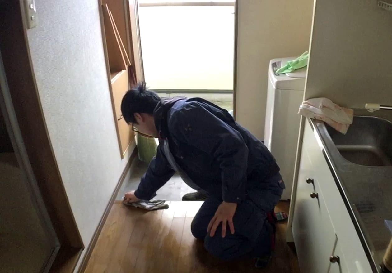 タオルで床を拭く宮井の様子