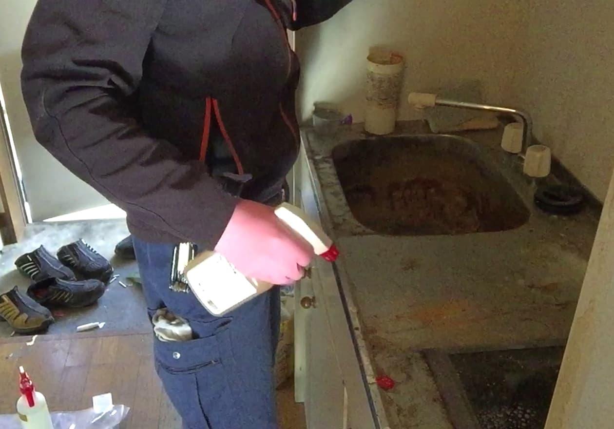キッチン台に洗剤を噴霧する宮井の様子