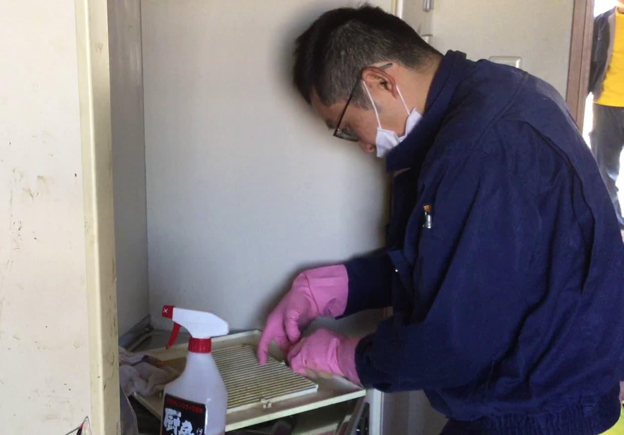 換気扇カバーを掃除する岡本の様子
