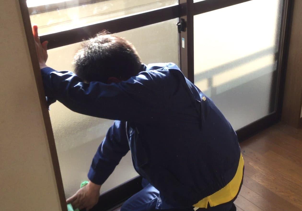 マイクロファイバークロスで窓を拭く高橋の様子