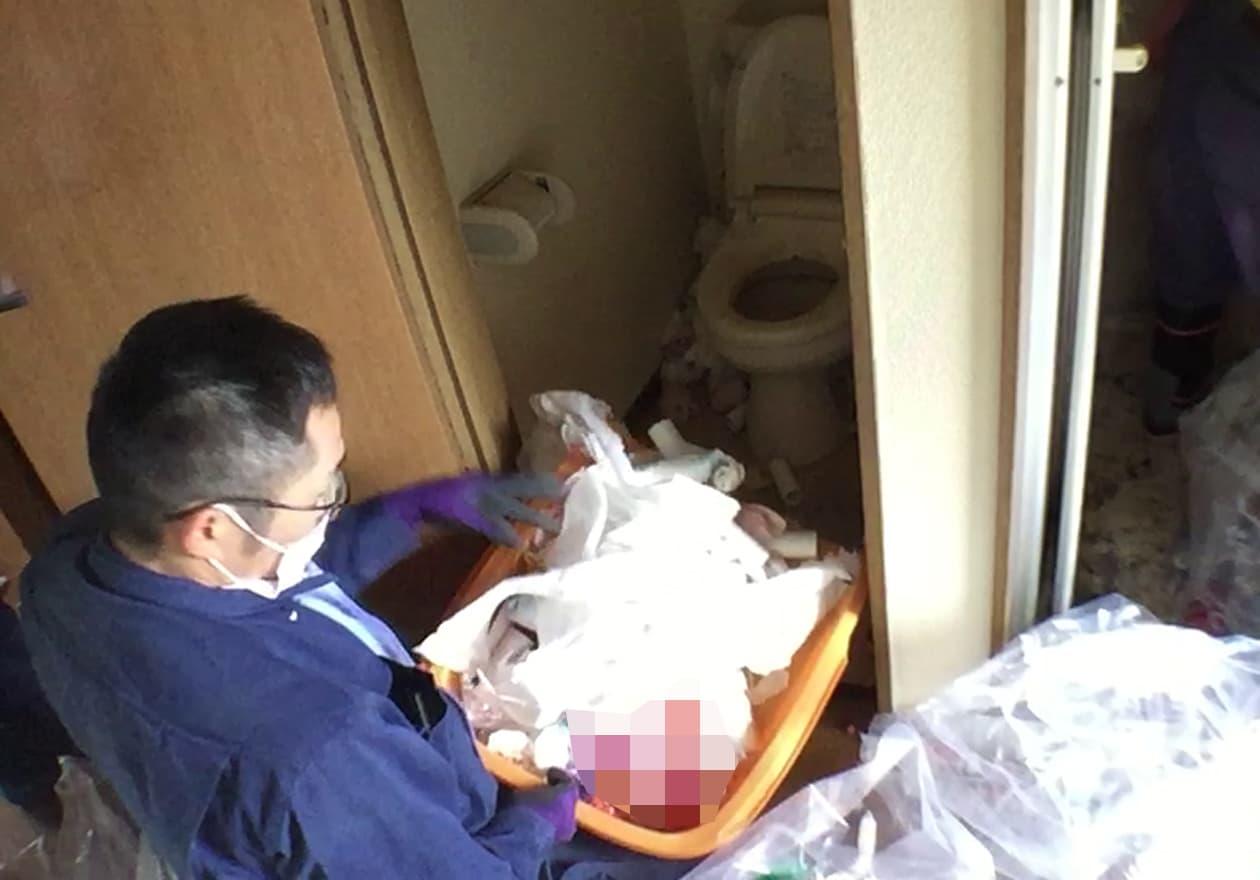 てみでトイレのゴミをすくう岡本の様子