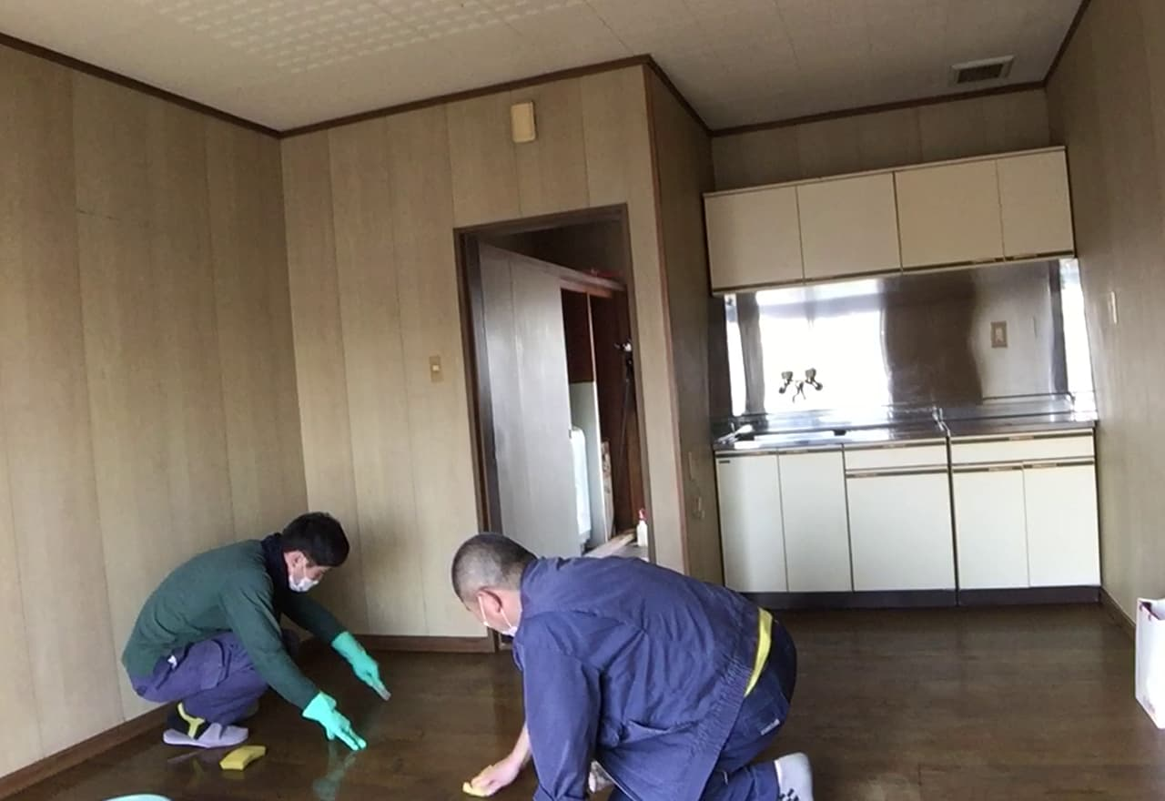 2名がかりでリビングの床の汚れを取り除いている様子