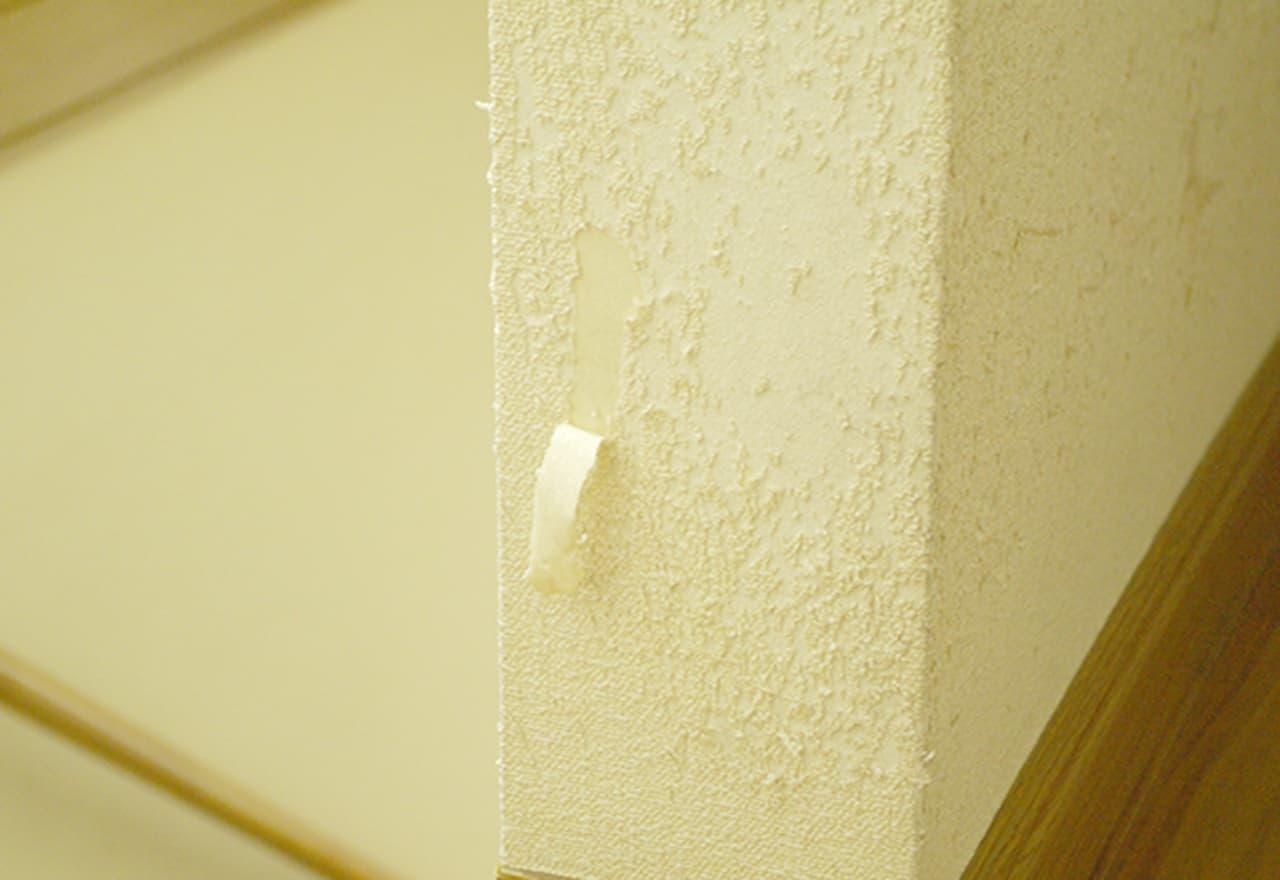 猫が爪とぎをしてボロボロになった壁の写真