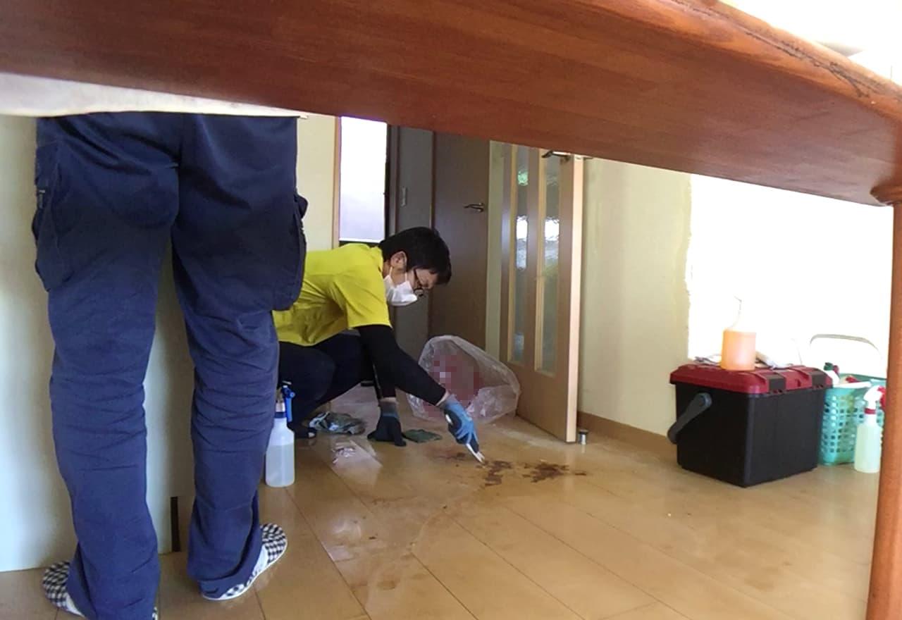 キッチン周辺の床をプラスチックヘラで掃除する様子