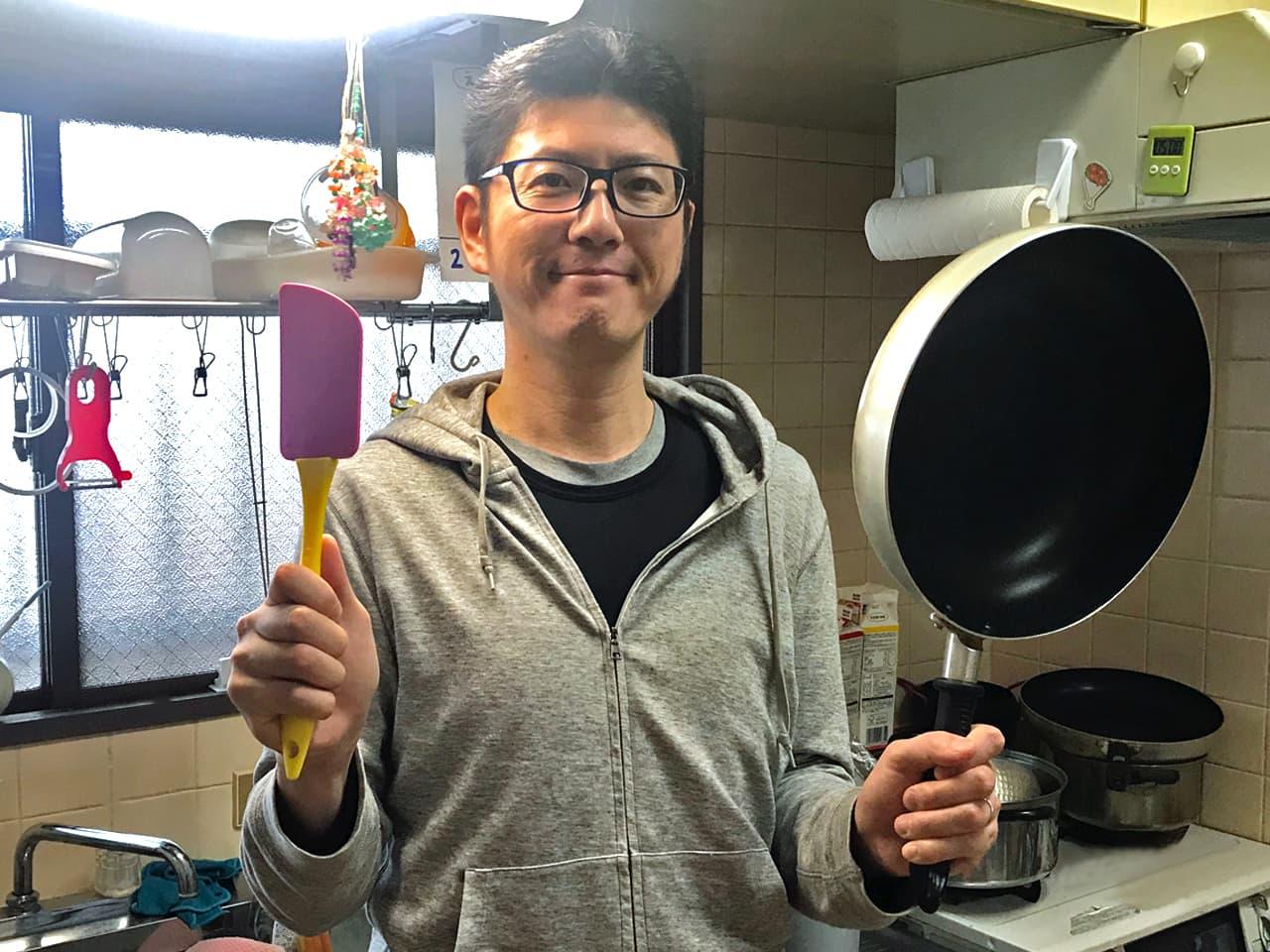 キッチンで調理道具を持った小田の写真