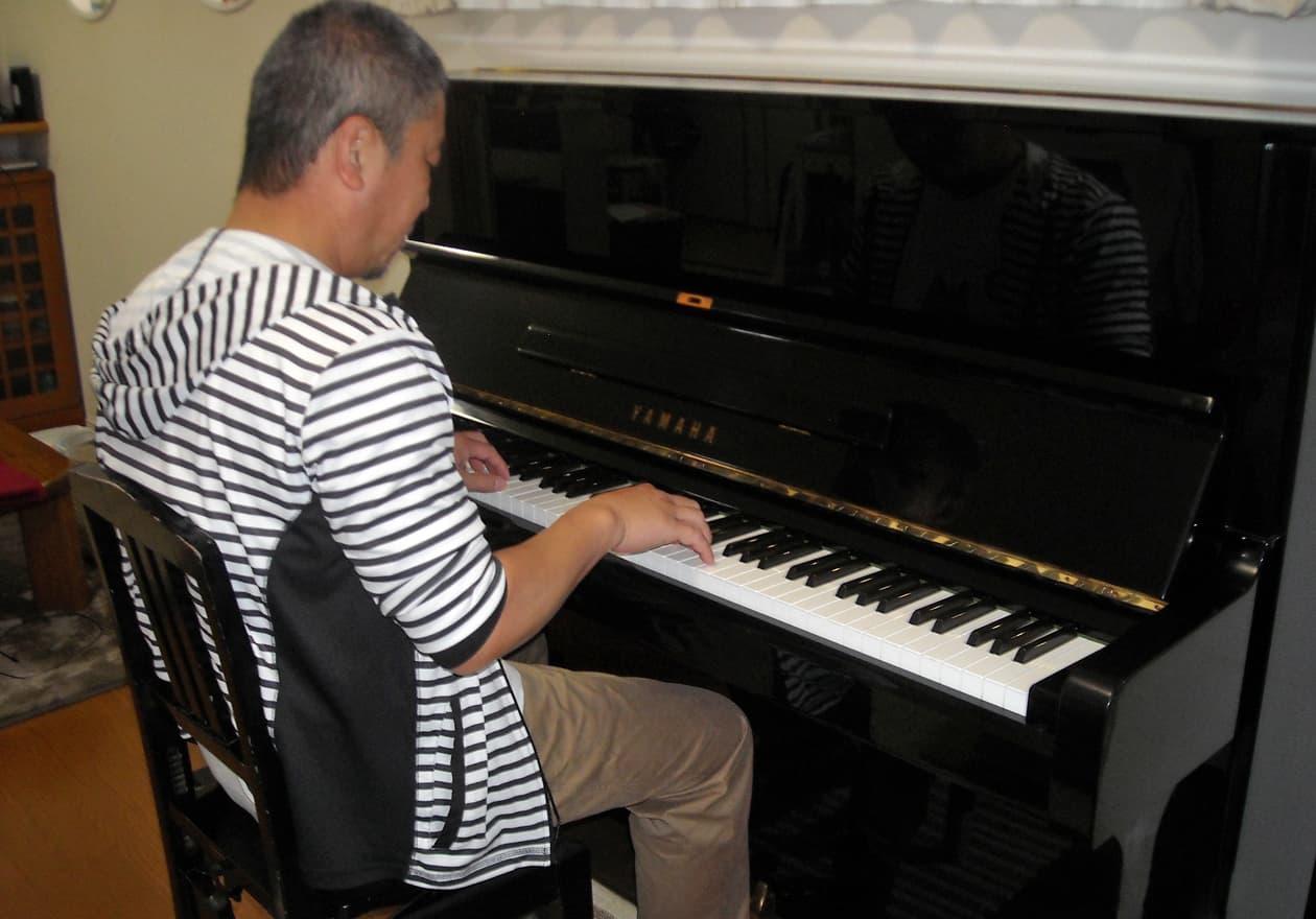 アップライトピアノを弾いている竹内の様子