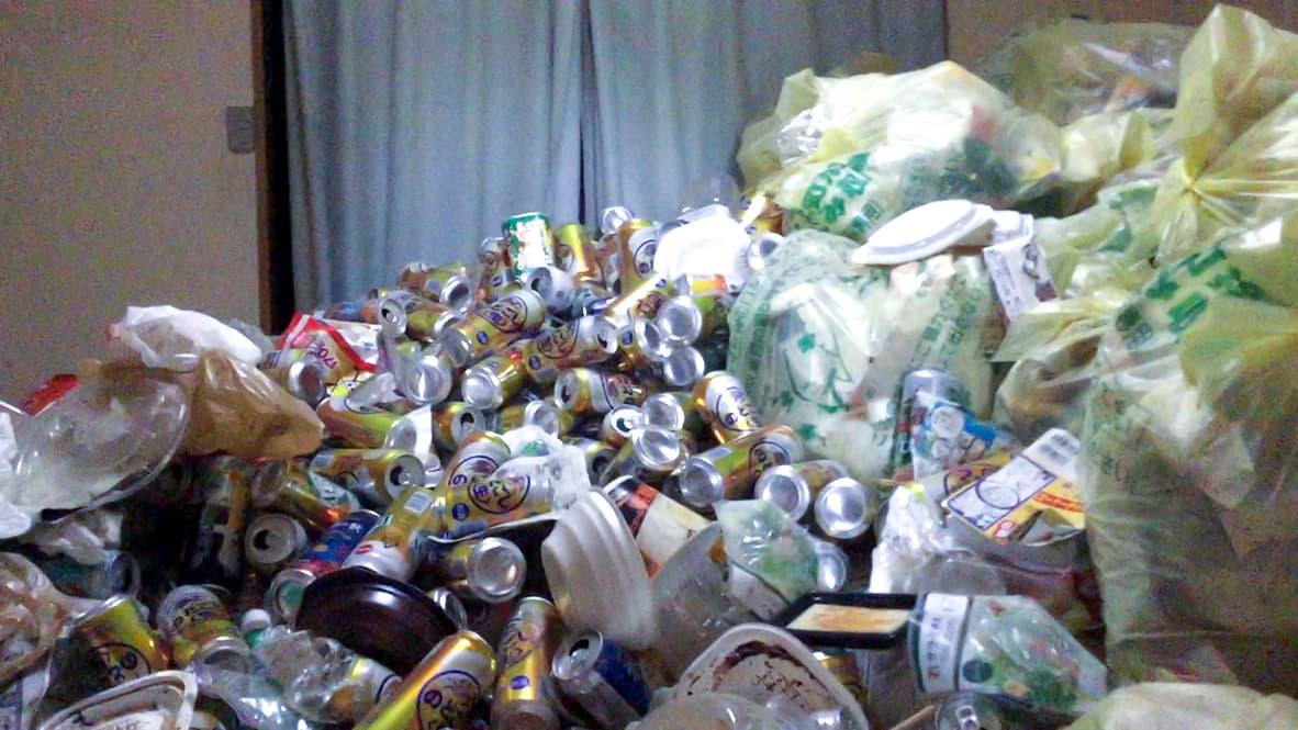 「5年分の生活ゴミ!ゴミ屋敷を片付け・清掃」リビングのビフォー写真(部屋一面、缶と袋が山になっている)