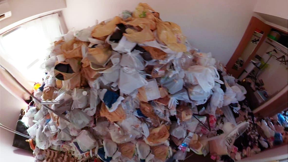 【名古屋市西区1K:片付け前】人の肩くらいまで袋が積み上がっているリビングの写真