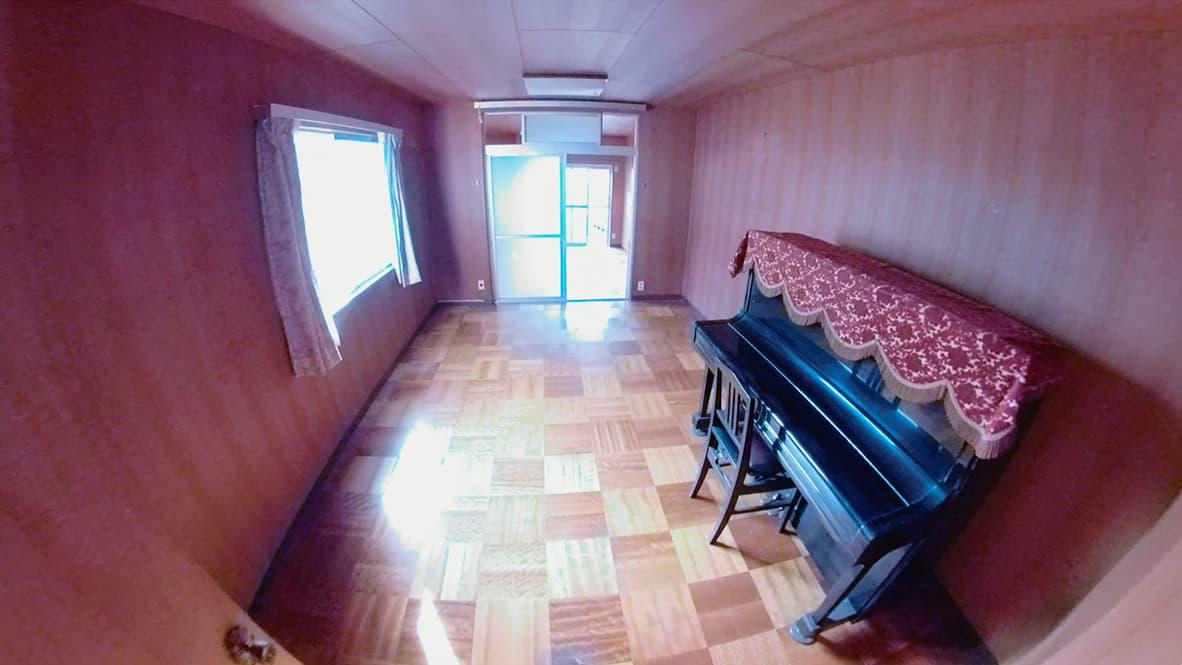 「ゴミ屋敷になってしまった実家の片付け」ピアノのある洋室のアフター写真(ピアノ以外のモノが全て無くなり、部屋の奥まで見渡せる)