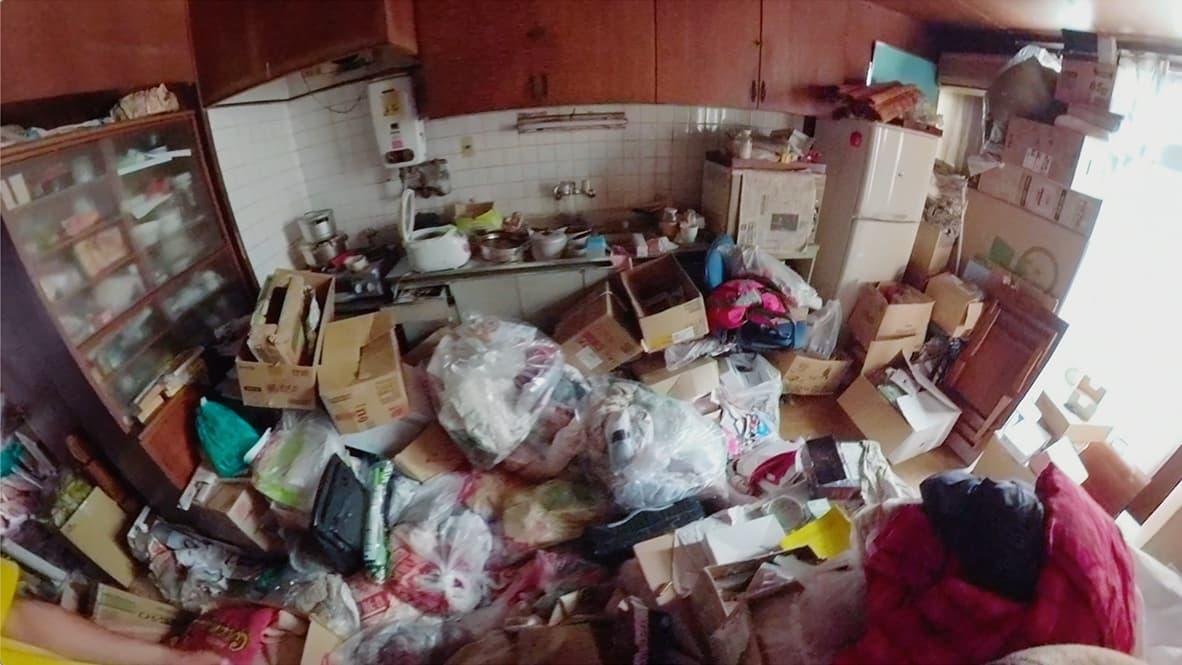 「ゴミ屋敷になってしまった実家の片付け」キッチンのビフォー写真(段ボールや袋が散乱している)