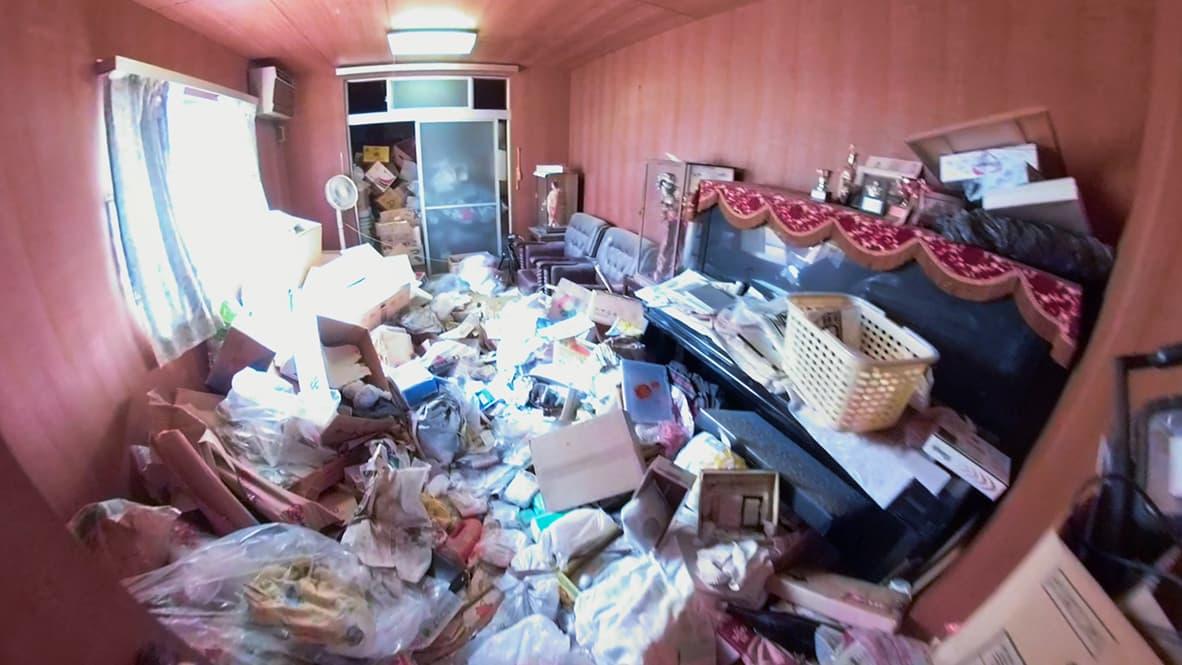「ゴミ屋敷になってしまった実家の片付け」ピアノのある洋室のビフォー写真(床が見えないほどモノがあふれている)