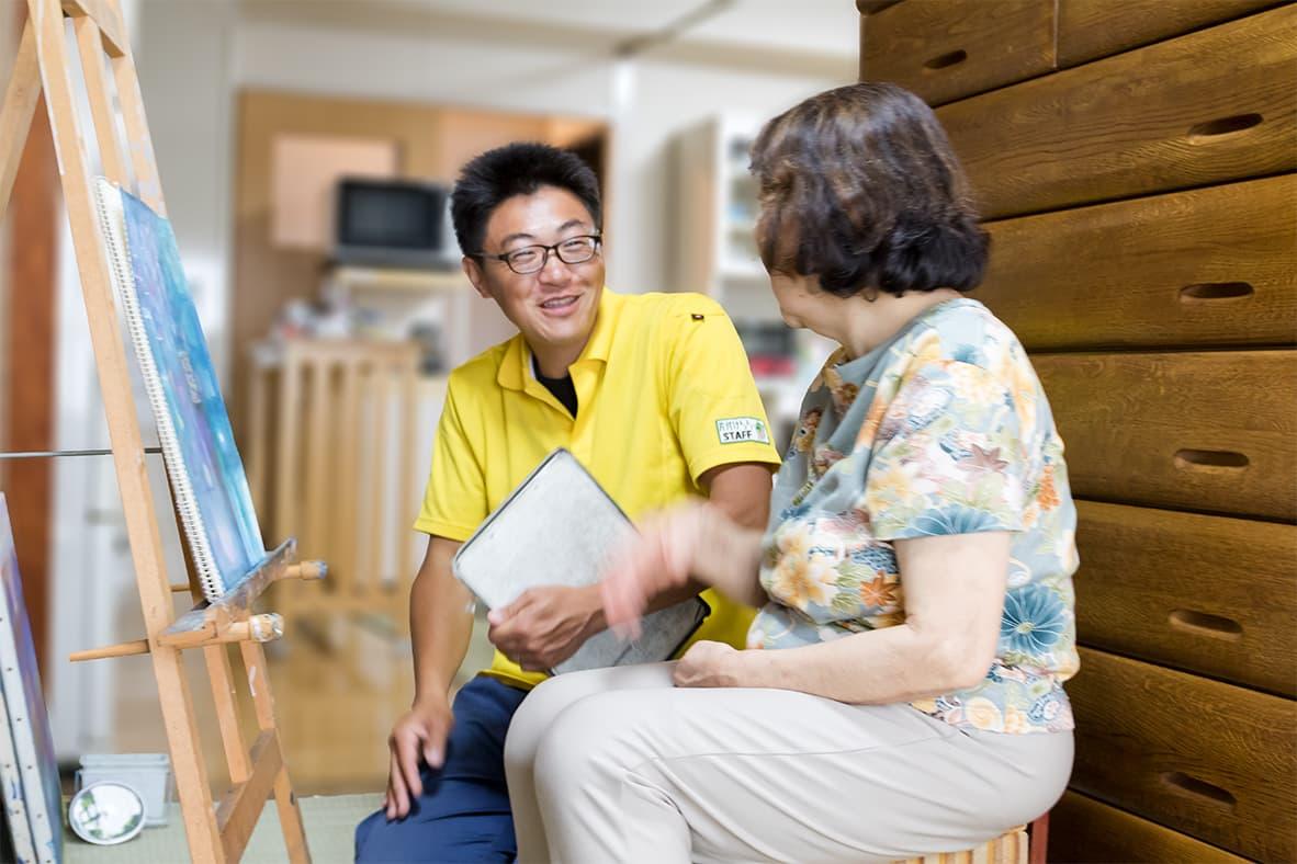 イーゼルの前で絵についてお話ししているお客さまと、満面の笑みで聞いている営業担当