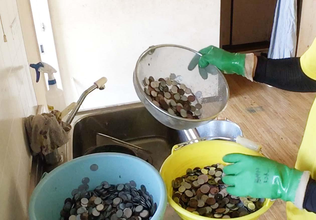 ザルを使って大量の小銭を洗っている写真