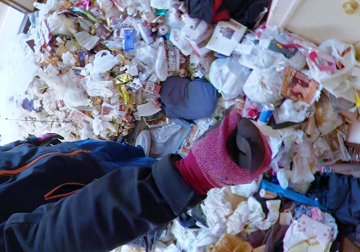 片付け前のリビングの床に、コンビニの袋や雑誌などが散らばっている写真