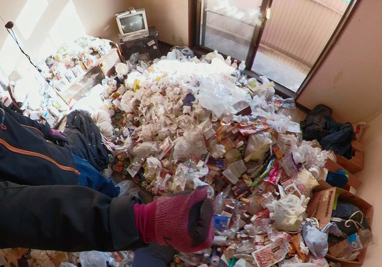 床にゴミなどが溜まっている、片付け前のリビングの写真
