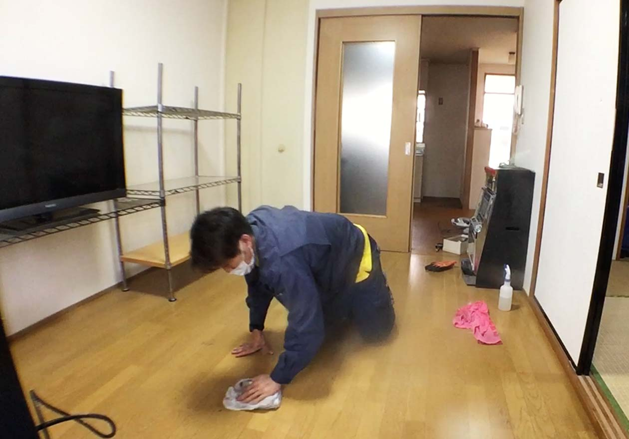 中性洗剤とタオルを使って床を拭いている写真